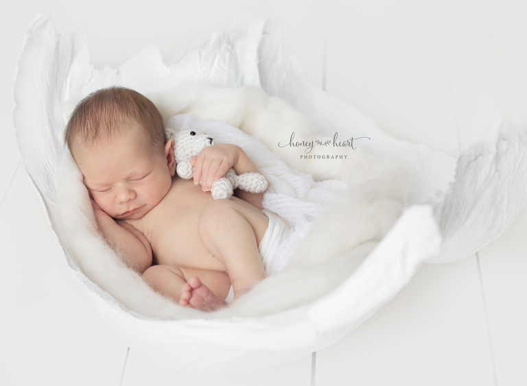 Calgary Newborn baby posed with knitted bear in a cast from mommys tummy