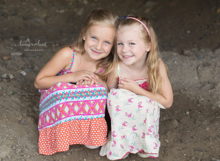 Sisters huddled together children's photography outdoor session in Calgary Alberta