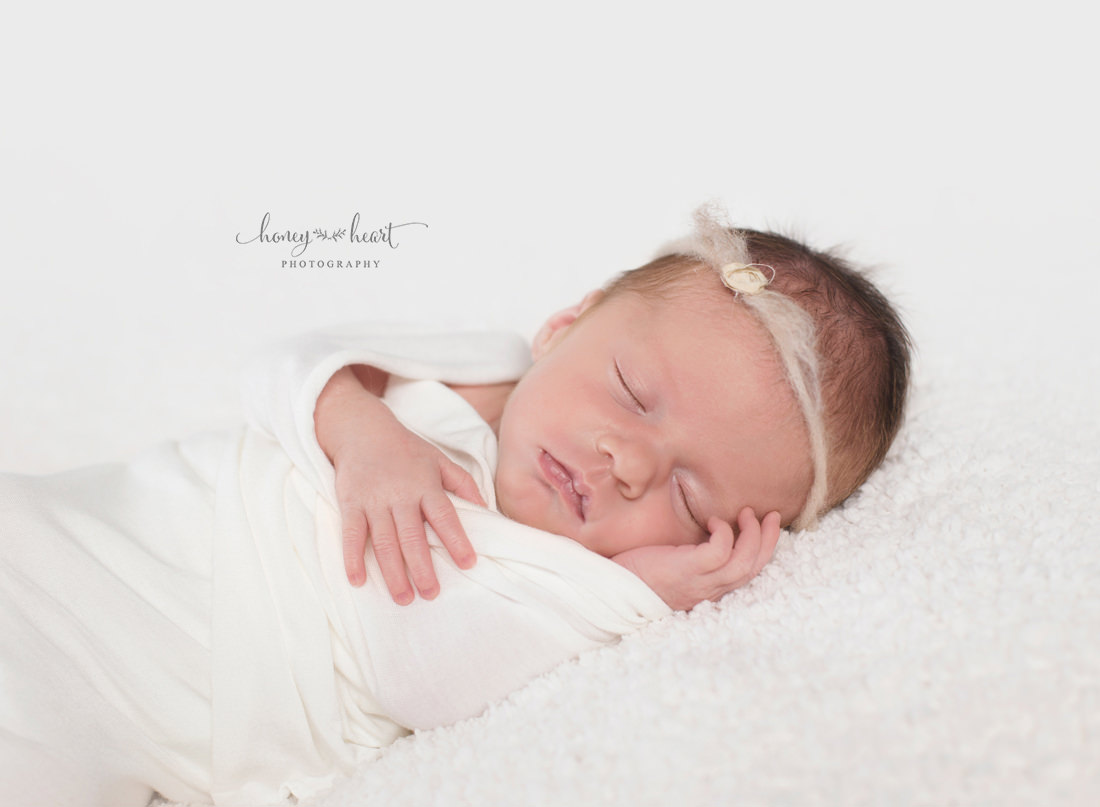 Peaceful sleeping newborn girl on cream textured blanket backdrop