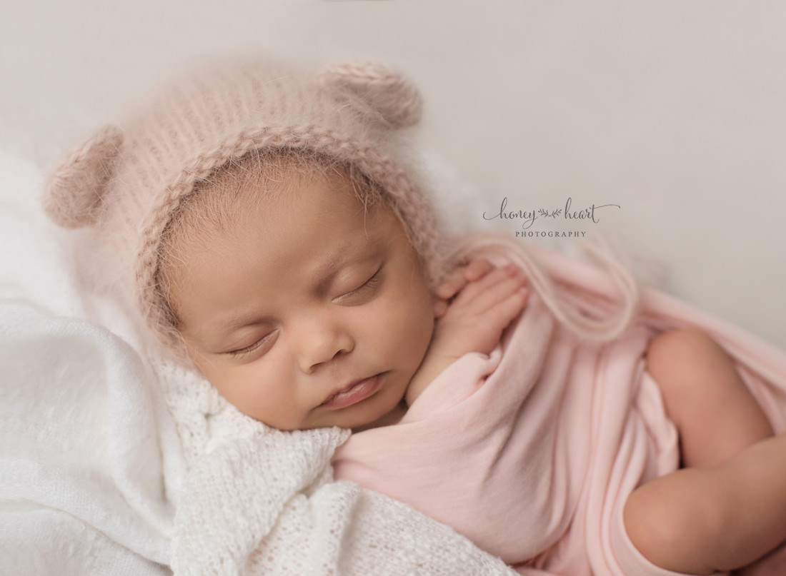 Baby girl wrapped in pink wearing angora bear bonnet and posed newborn photography studio session