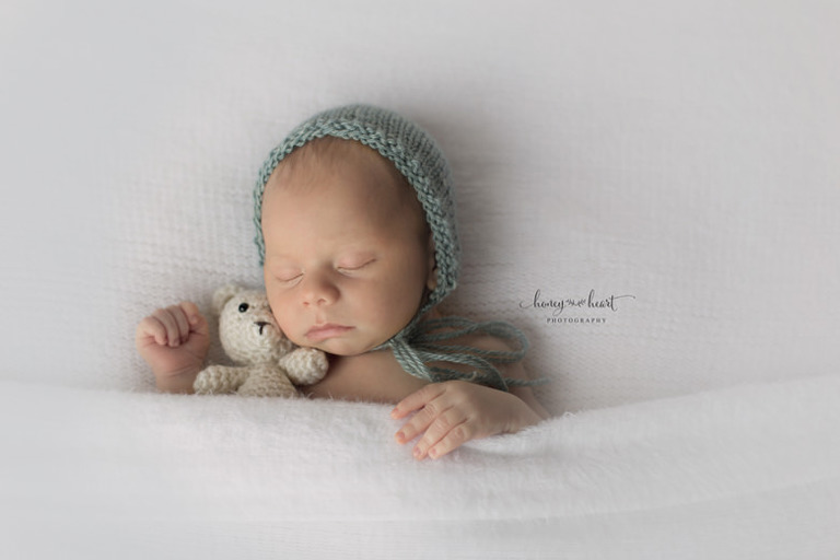 Sleeping Newborn tucked in blankets holding miniature crocheted teddy bear Newborn Photographer Calgary