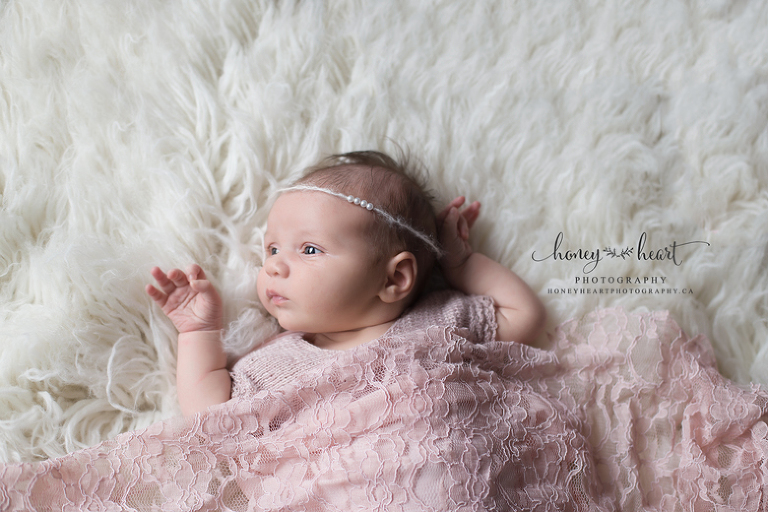 Awake newborn wrapped in pink and lace wearing pearls Calgary AB Simple Newborn Photography