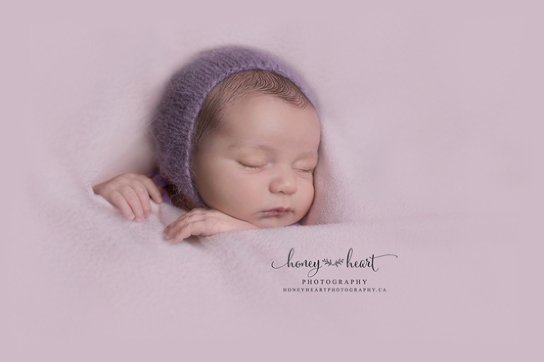 Sleeping newborn tucked in pose wearing lavendar purple knitted bonnet minimalist newborn photography Newborn Photographers SW Calgary