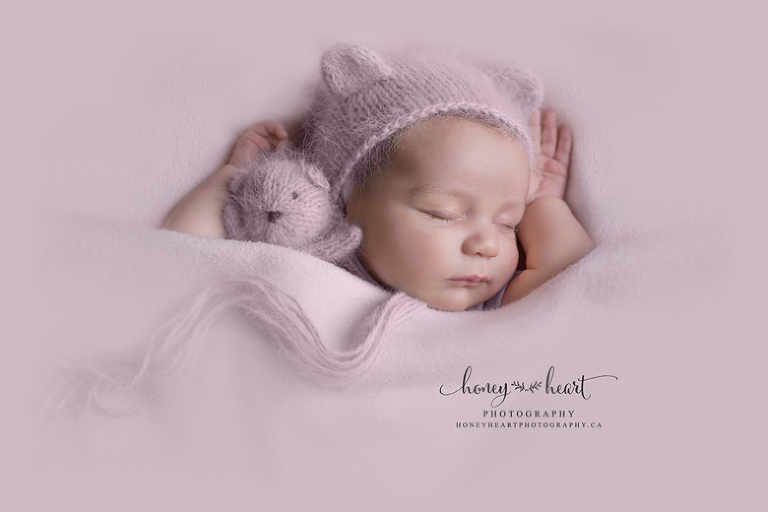 Sleeping newborn tucked in pose wearing blush pink knitted bonnet cuddling knitted bear Newborn Photographers SW Calgary