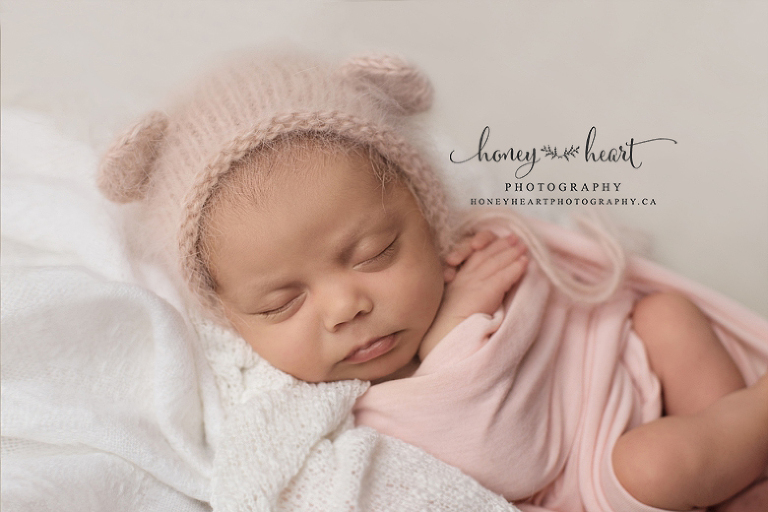 Baby girl wearing knitted angora bear bonnet in blush pink Calgary Alberta Newborn Photography session