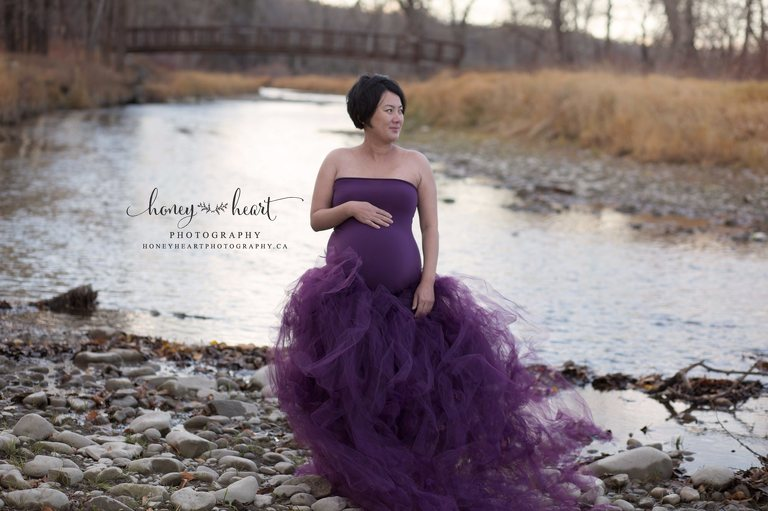 Pregnancy pictures by the water purple tulle skirt maternity dress standing by river water Calgary Maternity Newborn Photographer