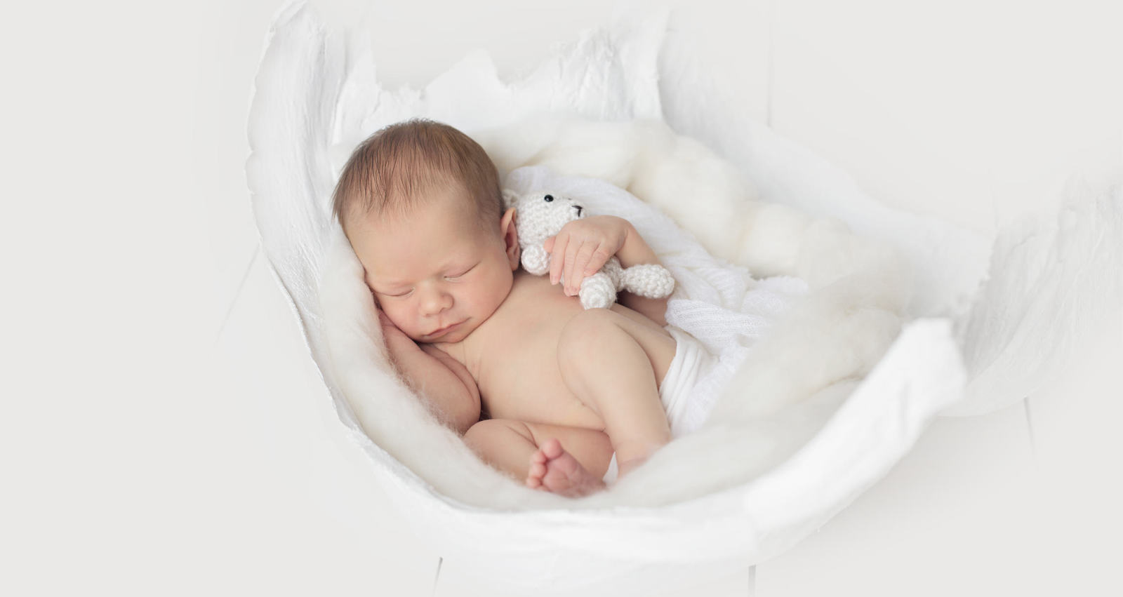 Newborn baby cuddled up in moms pregnancy belly cast newborn photography calgary photographer
