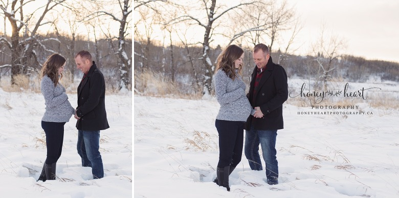 Soon to be parents holding hands posing maternity pictures in the snow at sunset calgary maternity photographer natural light photography