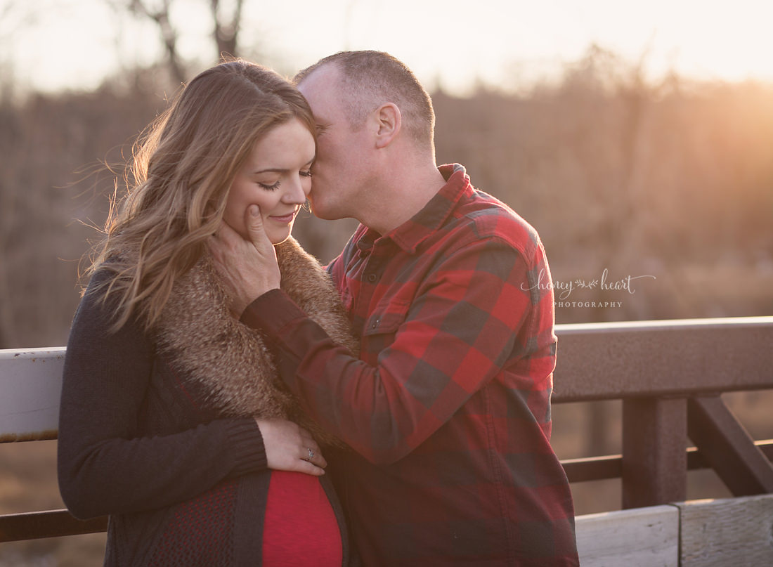 Expecting couple leaning on bridge during sunset maternity session early winter maternity pictures