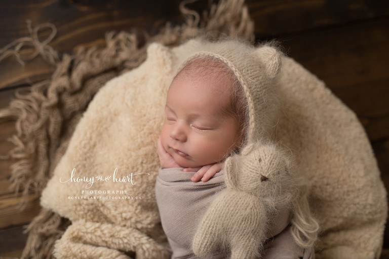 Sleeping newborn boy wrapped and posed with hand under chin Angora bear bonnet and matching knitted teddy bear - newborn session in Calgary studio Calgary Newborn Baby Photographer