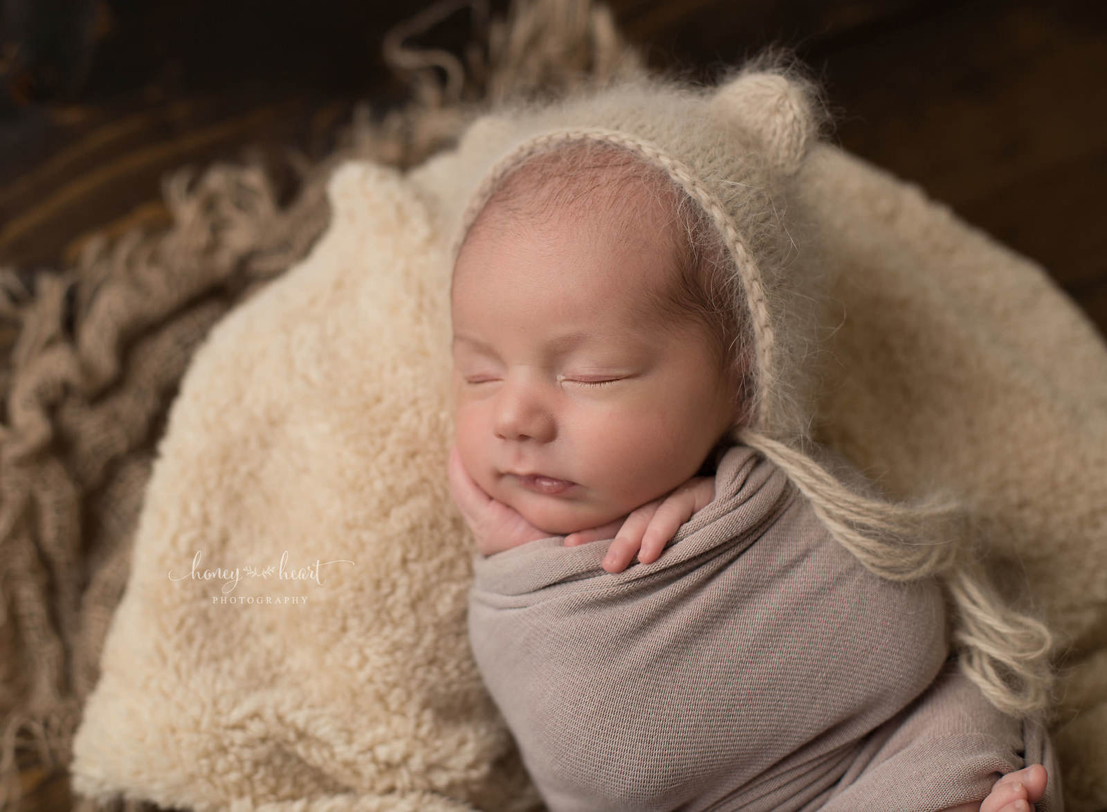 new baby wrapped in neutral earth tone colours wearing handmade knitted bonnet with ears newborn photographer calgary photography studio session