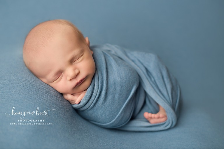 Baby sleeping side laying wrapped in blue wrap
