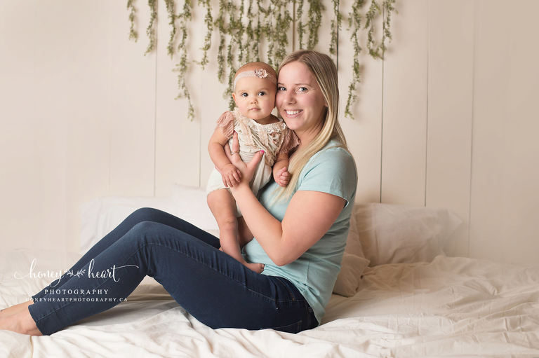 Mom holding baby girl up in studio photography session pastel and neutral colours Calgary Baby Photographer