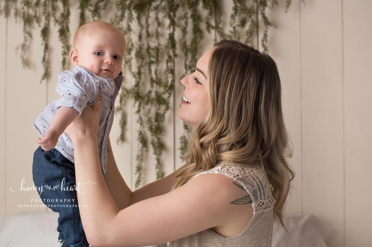 mom holding her baby up and interacting with smiling baby Calgary Baby Photography