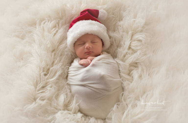 baby wrapped in white wrap laying on cream flokati wearing santa hat Calgary newborn photographers