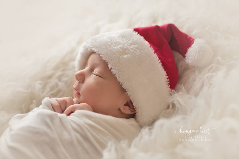 Newborn baby boy wearing santa hat side profile calgary baby photographers