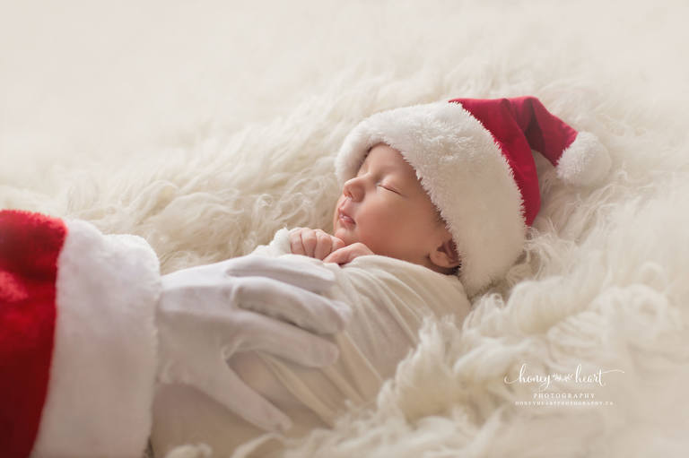 Newborn baby boy laying on cream flokati with santa hand holding him calgary newborn photography studio session South Calgary newborn photography